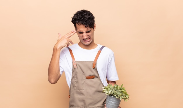 Giovane giardiniere uomo che sembra infelice e stressato, gesto di suicidio che fa segno di pistola con la mano, indicando la testa