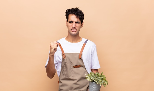 Uomo giovane giardiniere che grida in modo aggressivo con un'espressione arrabbiata o con i pugni chiusi per celebrare il successo