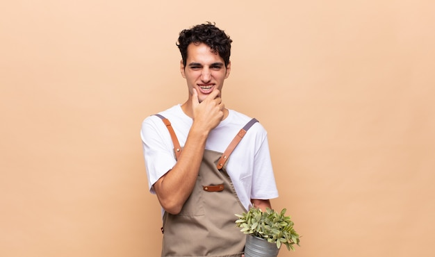 Giovane giardiniere uomo con la bocca e gli occhi spalancati e la mano sul mento, sentendosi spiacevolmente scioccato, dicendo cosa o wow