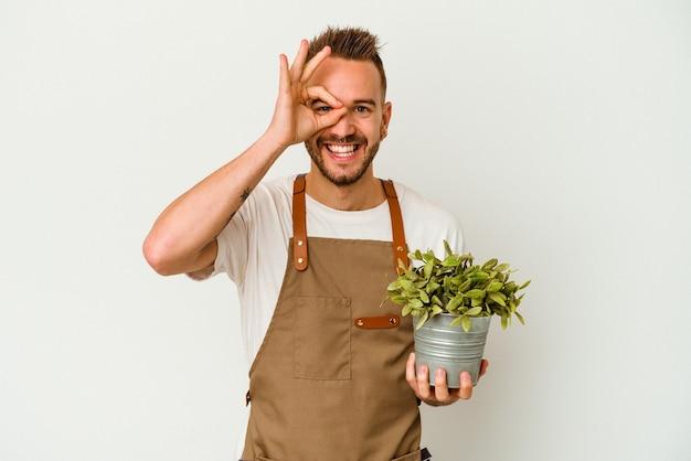 Il giovane giardiniere ha tatuato l'uomo caucasico che tiene una pianta isolata su fondo bianco eccitato mantenendo il gesto giusto sull'occhio.