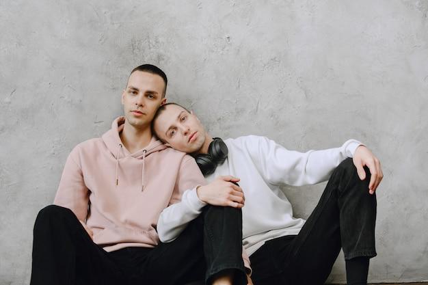 La giovane coppia gay seduta sul pavimento usando il laptop, usando le cuffie ascolta musica insieme, abbracciando o abbracciando.