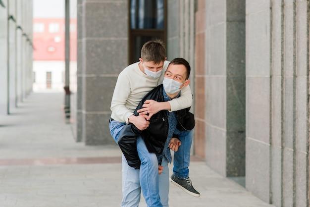 Giovani coppie gay che indossano mascherina medica che abbracciano alla città.