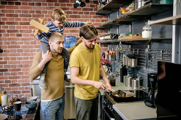 Giovane gay che cucina la colazione sul fornello in cucina quando suo marito fa un giro sulle spalle al loro figlioletto