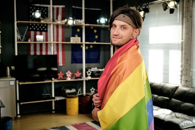 Giovane gay con bandiera dell'orgoglio in piedi nel soggiorno e guardando la telecamera
