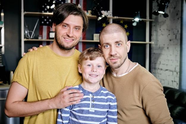 Giovani genitori gay e il loro figlioletto in piedi in appartamento e sorridono alla telecamera