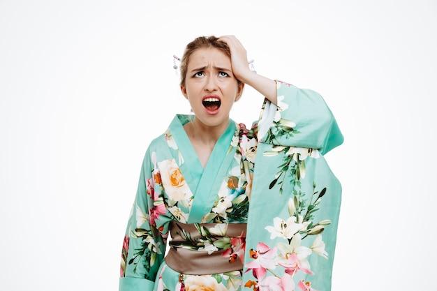 Giovane donna geisha nel tradizionale kimono giapponese che sembra eccitata e frustrata tenendo la mano sulla testa gridando in preda al panico in piedi sul muro bianco