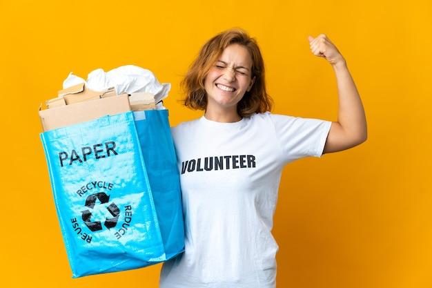 Giovane ragazza georgiana che tiene un sacchetto di riciclaggio pieno di carta da riciclare facendo un gesto forte