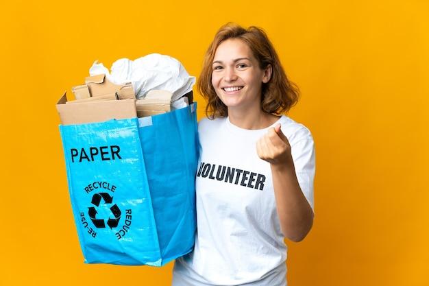 Giovane ragazza georgiana in possesso di un sacchetto di riciclaggio pieno di carta per riciclare facendo gesto di denaro