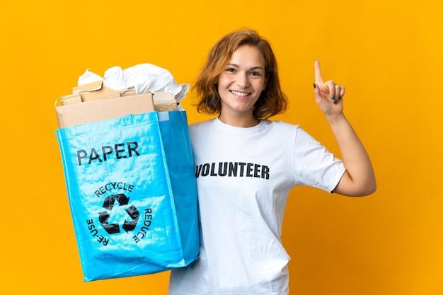 Giovane ragazza georgiana che tiene un sacchetto di riciclaggio pieno di carta da riciclare indicando una grande idea