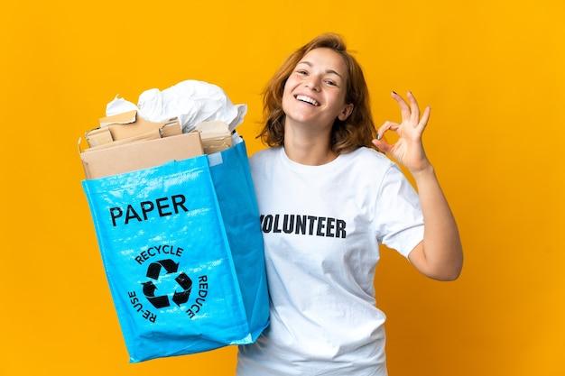 Giovane ragazza georgiana che tiene un sacchetto di riciclaggio pieno di carta da riciclare che mostra segno giusto con le dita