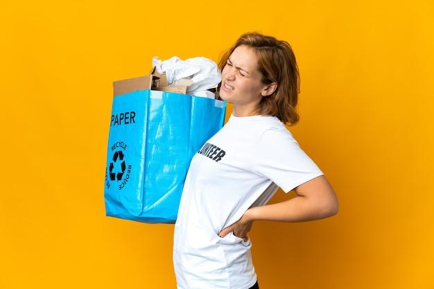 Giovane ragazza georgiana che tiene un sacchetto di riciclaggio pieno di carta per riciclare che soffrono di mal di schiena