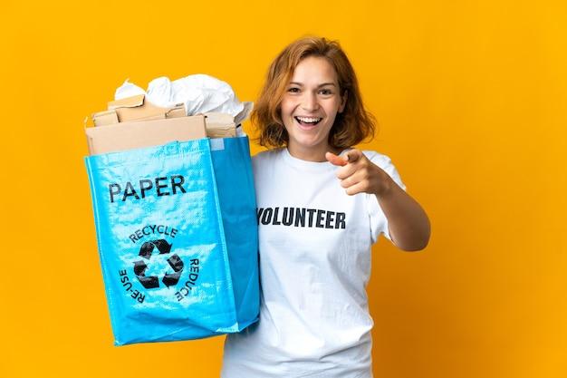 Giovane ragazza georgiana che tiene un sacchetto di riciclaggio pieno di carta da riciclare sorpreso e rivolto verso la parte anteriore