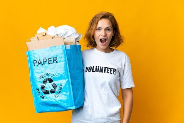 Giovane ragazza georgiana che tiene un sacchetto di riciclaggio pieno di carta da riciclare con l'espressione facciale di sorpresa