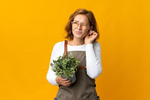 Giovane donna georgiana in possesso di una pianta isolata su sfondo giallo frustrata e che copre le orecchie