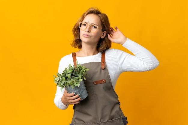 Giovane donna georgiana in possesso di una pianta isolata su sfondo giallo con dubbi
