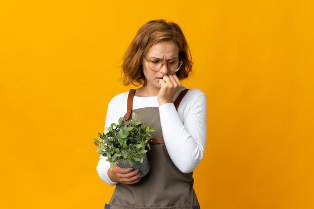 Giovane donna georgiana in possesso di una pianta isolata su sfondo giallo con dubbi Foto Premium