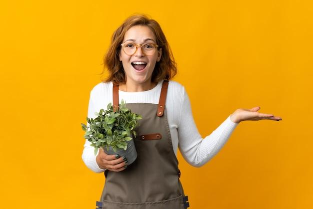 Giovane donna georgiana che tiene una pianta isolata su sfondo giallo con espressione facciale scioccata