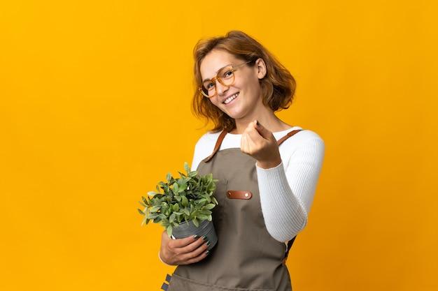 Giovane donna georgiana che tiene una pianta isolata sulla parete gialla che fa gesto dei soldi