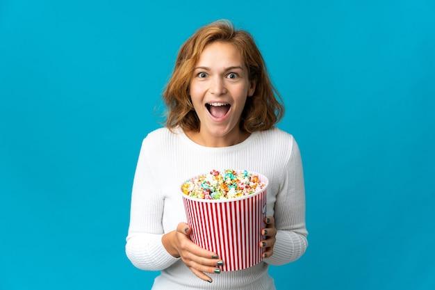 Giovane donna georgiana isolata su priorità bassa blu che tiene un grande secchio di popcorn