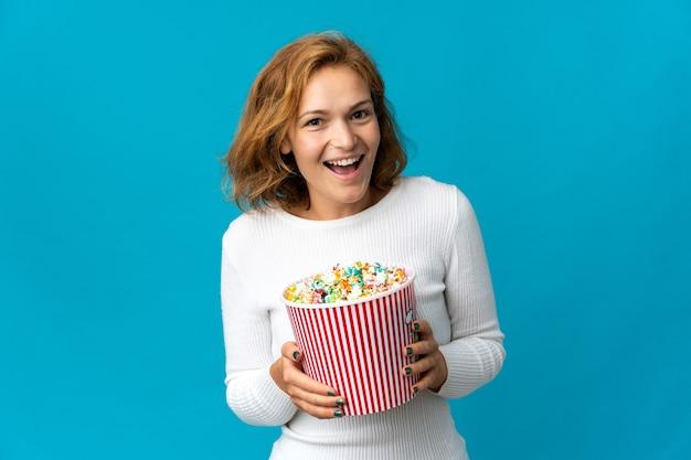 Giovane donna georgiana isolata sulla parete blu che tiene un grande secchio di popcorn
