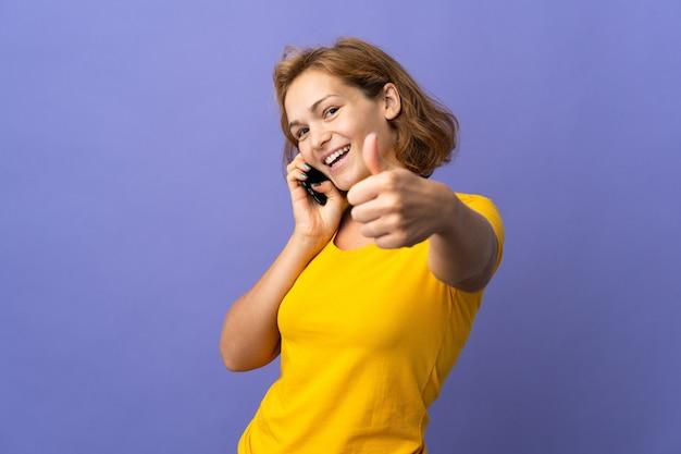 Giovane donna georgiana isolata mantenendo una conversazione con il cellulare mentre si fa i pollici in su