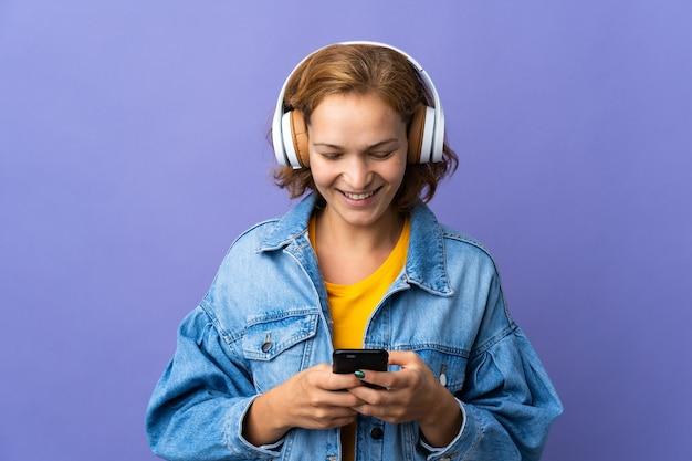 Giovane donna georgiana isolata su sfondo viola ascoltando musica e guardando al cellulare