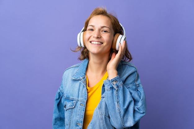 Giovane donna georgiana isolata sulla musica d'ascolto della parete viola