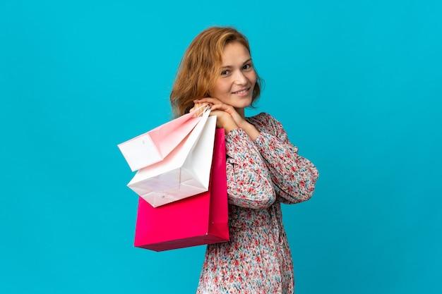 Giovane donna georgiana con la borsa della spesa isolata su sfondo blu che tiene le borse della spesa