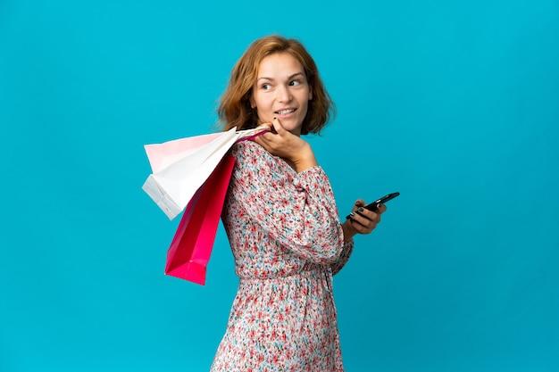 Giovane donna georgiana con il sacchetto della spesa isolato