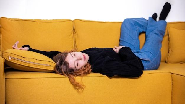 La giovane ragazza dello zenzero in maglione nero e blue jeans sta dormendo su un divano giallo a casa