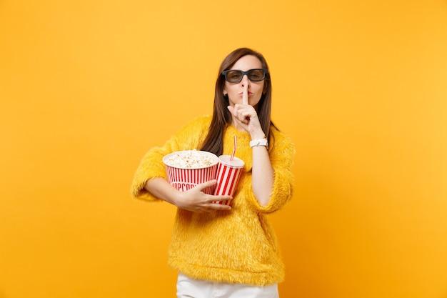 Giovane ragazza in occhiali 3d imax che guarda film film che tiene secchio di popcorn tazza di soda dicendo silenzio stai zitto con il dito sulle labbra, gesto shhh isolato su sfondo giallo. le emozioni delle persone nel cinema.