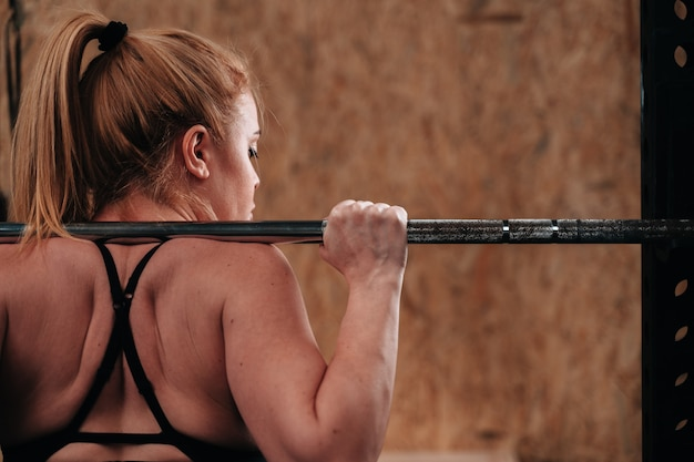 Giovane ragazza sullo sfondo di una palestra crossfit facendo un allenamento a peso morto.