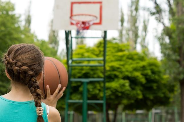 Giovane ragazza giocatore di basket prendendo la mira con la palla