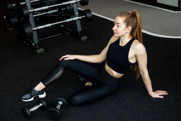 La ragazza in abiti sportivi neri è impegnata in palestra con il fitness club di manubri