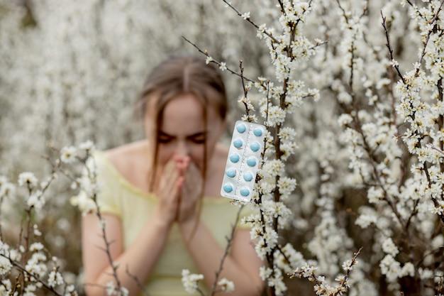 Giovane ragazza che soffia il naso e starnuti nel tessuto davanti all'albero in fiore. allergeni stagionali che colpiscono le persone. la bella signora ha la rinite.