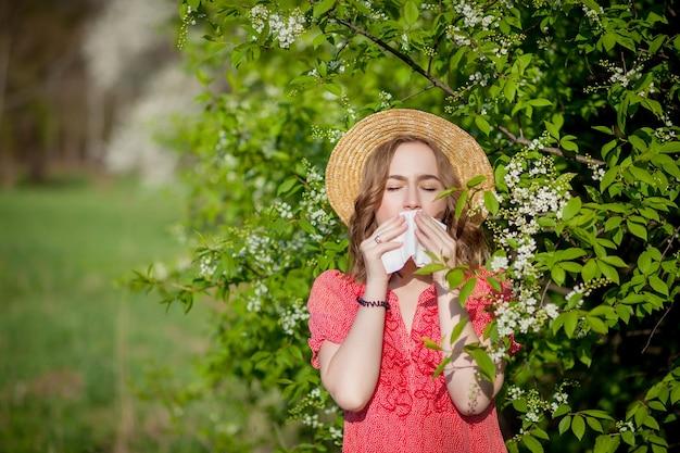 Ragazza giovane soffiando il naso e starnuti nel tessuto davanti all'albero in fiore.