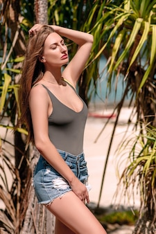 Giovane ragazza in blue jeans stare vicino a palme tropicali