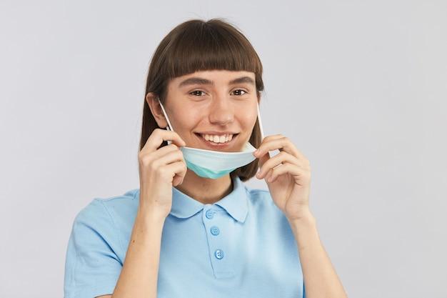 Giovane ragazza in maglietta blu sul muro grigio togliere la maschera di protezione e sorridere alla telecamera, copia dello spazio