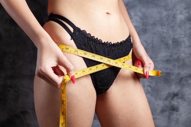 La ragazza in reggiseni misura la pancia con del nastro adesivo