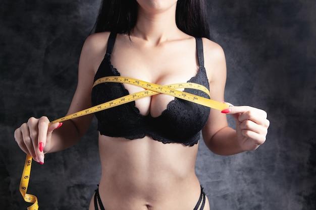 La ragazza in reggiseni misura il seno