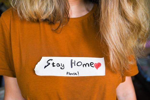 Giovane ragazza in una maglietta marrone con una scritta rimanere a casa. la ragazza esorta a rimanere a casa durante la pandemia. concetto di autoisolamento