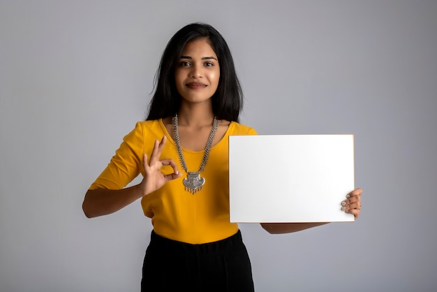 Una giovane ragazza o donna d'affari con un cartello in mano su un muro grigio.