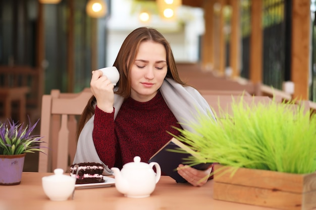 La ragazza in caffè si siede e beve il tè con il dessert