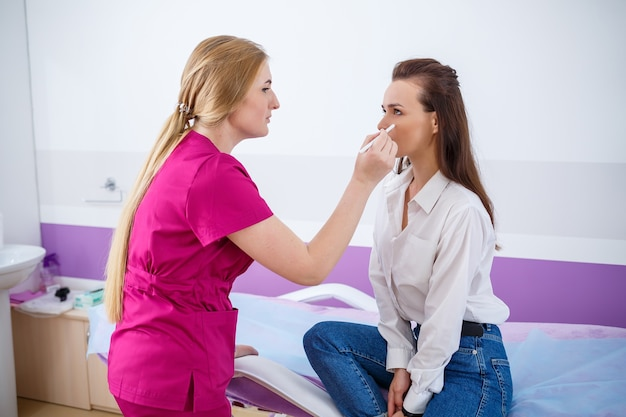Una ragazza è venuta in clinica per un appuntamento con un medico qualificato, un cosmetologo specializzato. il medico esamina le condizioni della pelle del viso del paziente