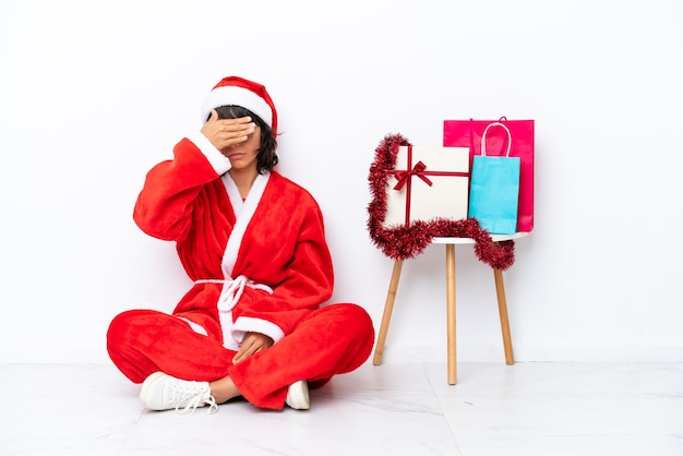 Giovane ragazza che celebra il natale seduto sul pavimento isolato su sfondo bianco che copre gli occhi con le mani. non voglio vedere qualcosa