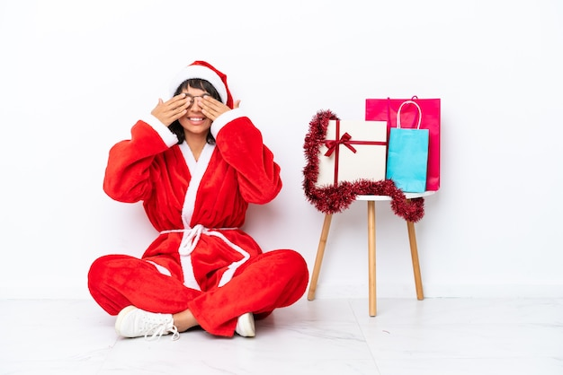 Giovane ragazza che celebra il natale seduta sul pavimento isolato su sfondo bianco che copre gli occhi con le mani