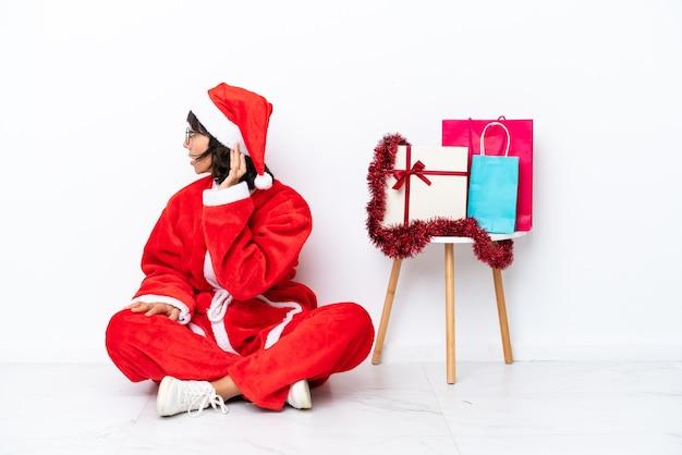 Giovane ragazza che celebra il natale seduta sul pavimento isolato su sfondo bianco ascoltando qualcosa mettendo la mano sull'orecchio
