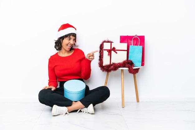 Giovane ragazza che celebra il natale seduta sul pavimento isolato su sfondo bianco che punta il dito di lato e presenta un prodotto