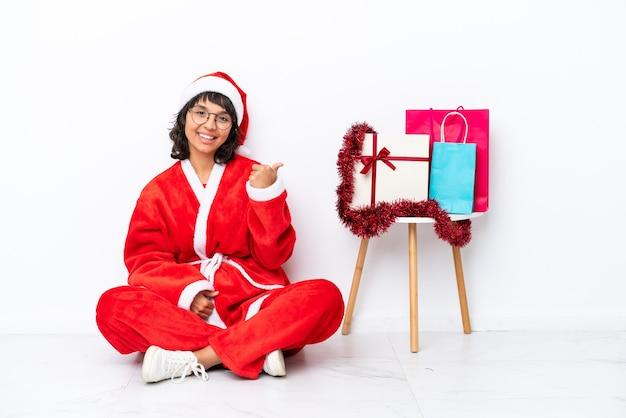 Giovane ragazza che celebra il natale seduta sul pavimento isolato su sfondo bianco che punta al lato per presentare un prodotto