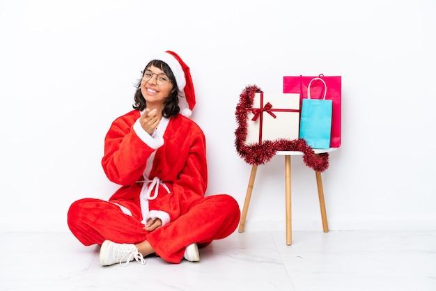 La giovane ragazza che celebra il natale seduta sul pavimento isolato su sfondo bianco punta il dito contro di te con un'espressione sicura